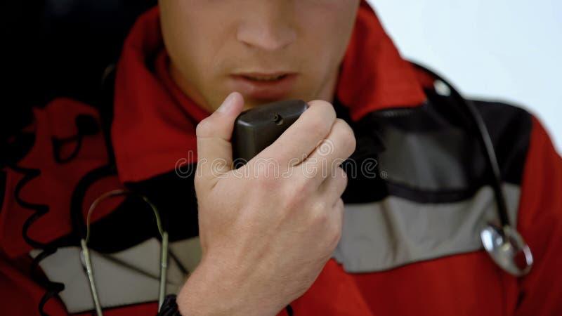 Мужской доктор отвечает радио в машине скорой помощи, срочном звонке к аварии, крупному плану стоковые изображения rf
