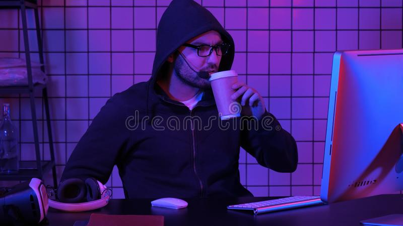 Мужской с капюшоном gamer наблюдая игру на компьютере стоковые изображения