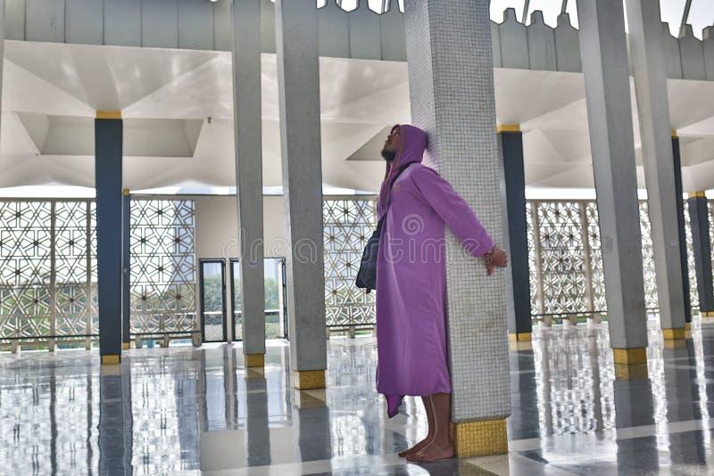 Мужской турист в национально мечети города Куалаа-Лумпур стоит около столбца и наслаждается красотой  стоковые изображения rf