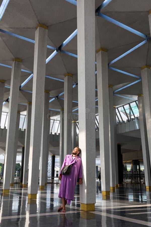 Мужской турист в национально мечети города Куалаа-Лумпур стоит около столбца и наслаждается красотой  стоковое фото rf