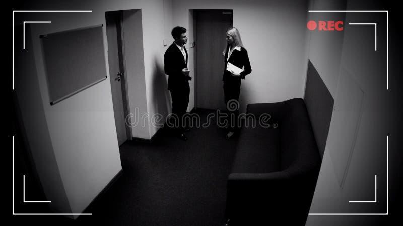 Мужчина и женские коллеги говоря коридор офиса, влияние камеры CCTV, отснятый видеоматериал стоковое фото rf