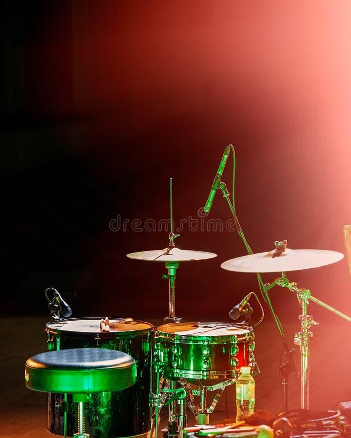 Музыкальные набор и микрофоны барабанчика в концертном зале на этапе стоковая фотография rf