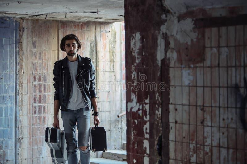 Музыкант улицы держа случай с гитарой и усилителем Пошл вниз к подземному переходу Бродячий образ жизни Игра для того чтобы зараб стоковая фотография rf