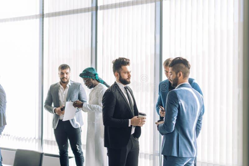 Мульти-этнические мужские коллеги стоят около больших окон говоря обсуждающ проекты стоковая фотография rf
