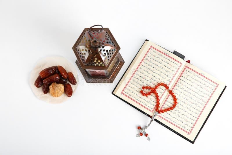 Мусульманские лампа, даты, Koran и шарики молитве на белой предпосылке стоковые изображения