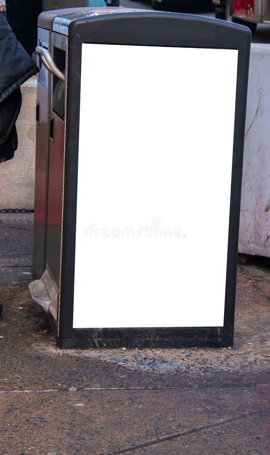 Мусорный бак на улице города с белым пустым знаком на ем бортовой стоковая фотография