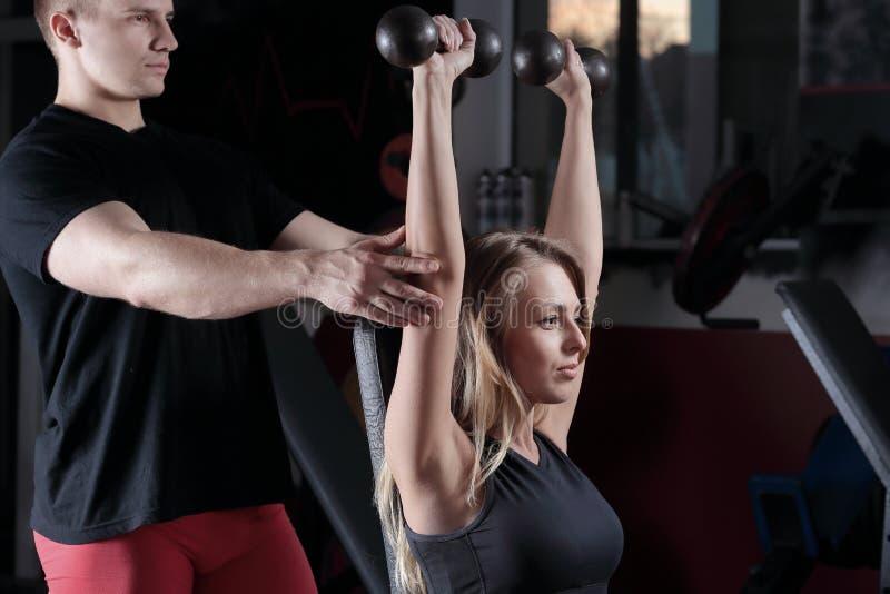 Мышечный тренер человека в футболке показывает молодую красивую женщину, как сделать тренировки стоковое изображение rf
