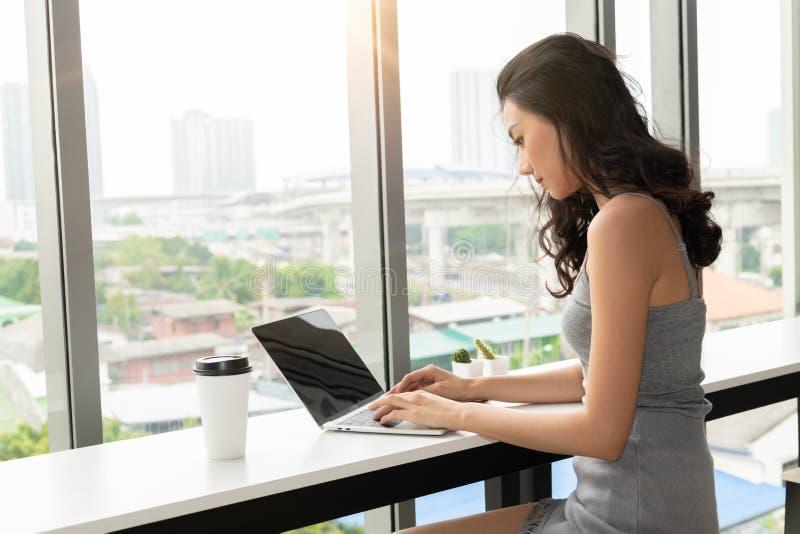 Молодая азиатская женщина используя ноутбук в кофейне, включает путь клиппирования экрана стоковая фотография