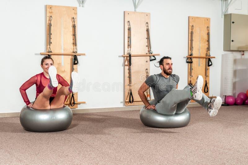 Молодая атлетическая разминка пар фитнеса и работать на шарике pilates с людьми нерезкости движения реальными стоковое изображение rf