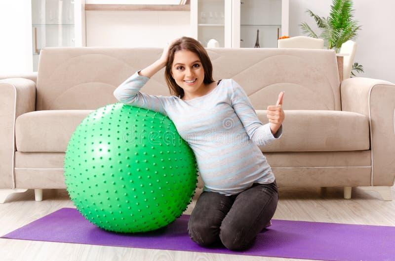 Молодая беременная женщина делая тренировки спорта дома стоковое изображение rf