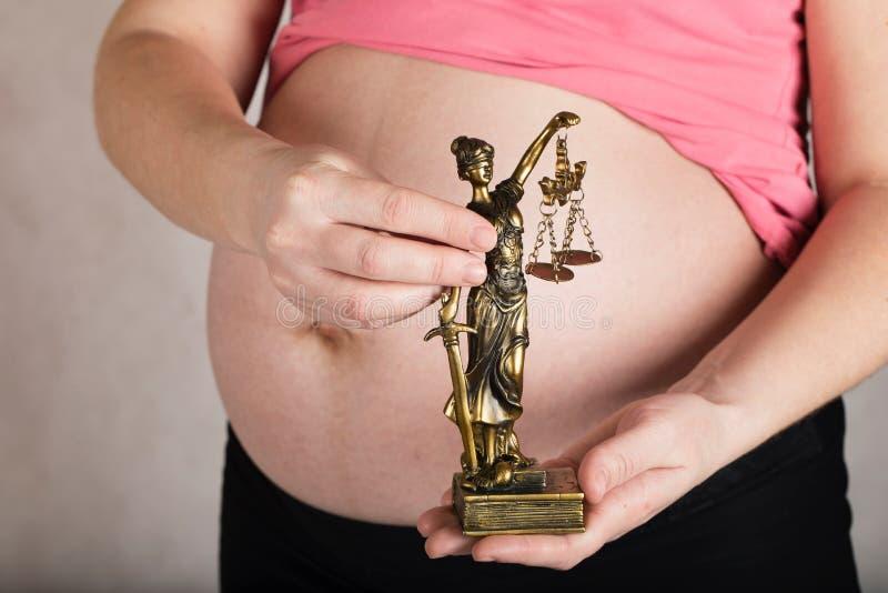 Молодая беременная женщина держит статую Themis стоковые изображения