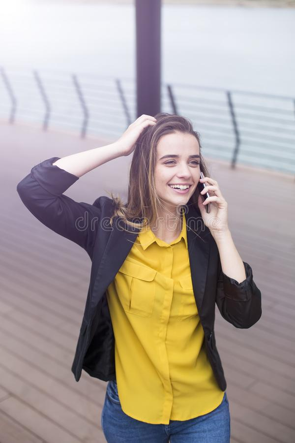 Молодая бизнес-леди использует мобильный телефон на улице стоковая фотография