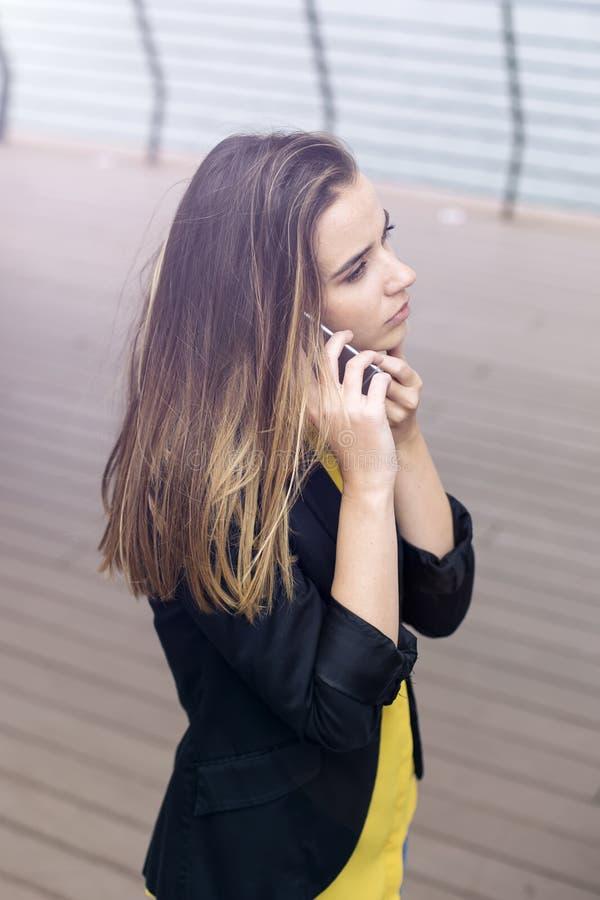 Молодая бизнес-леди использует мобильный телефон на улице стоковые изображения