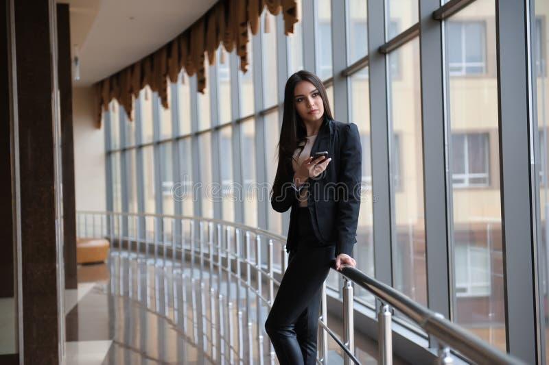 Молодая женщина брюнет смотрит через окно на самолетах и ждет к отклонению в авиапорте стоковое изображение