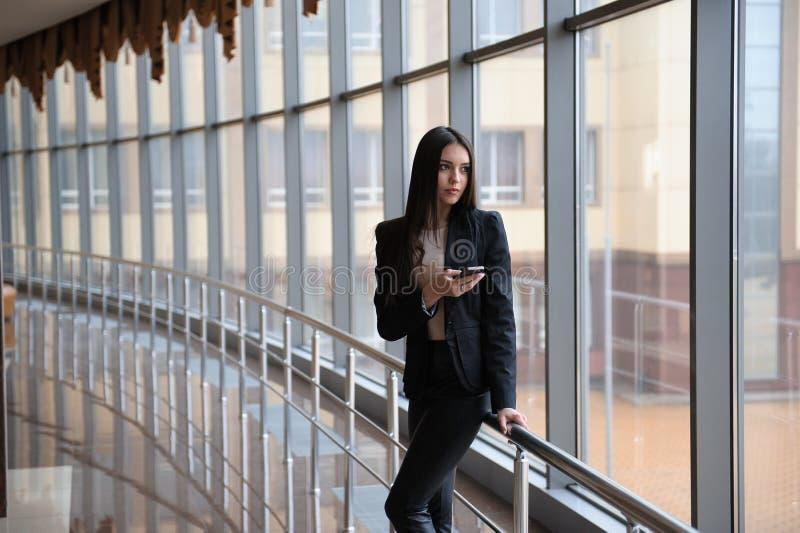 Молодая женщина брюнет смотрит через окно на самолетах и ждет к отклонению в авиапорте стоковые фото