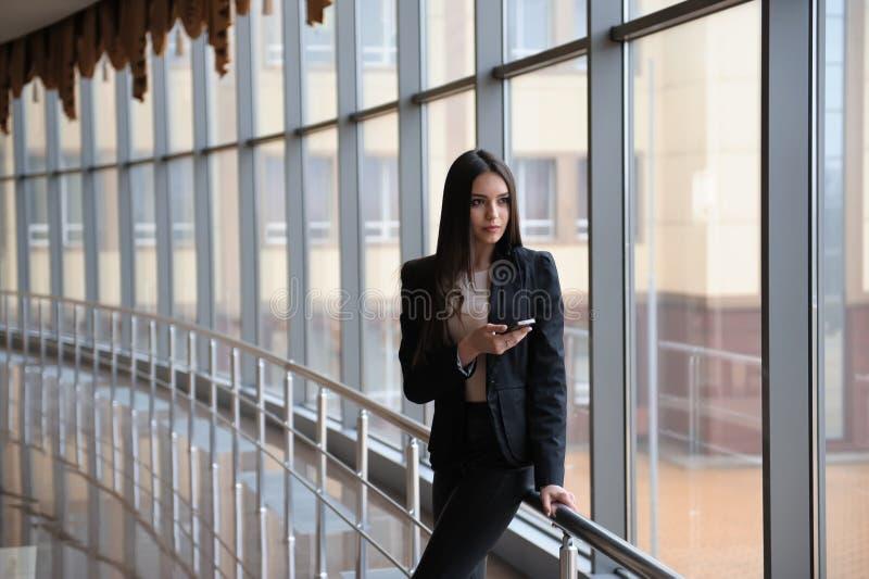 Молодая женщина брюнет смотрит через окно на самолетах и ждет к отклонению в авиапорте стоковое фото rf