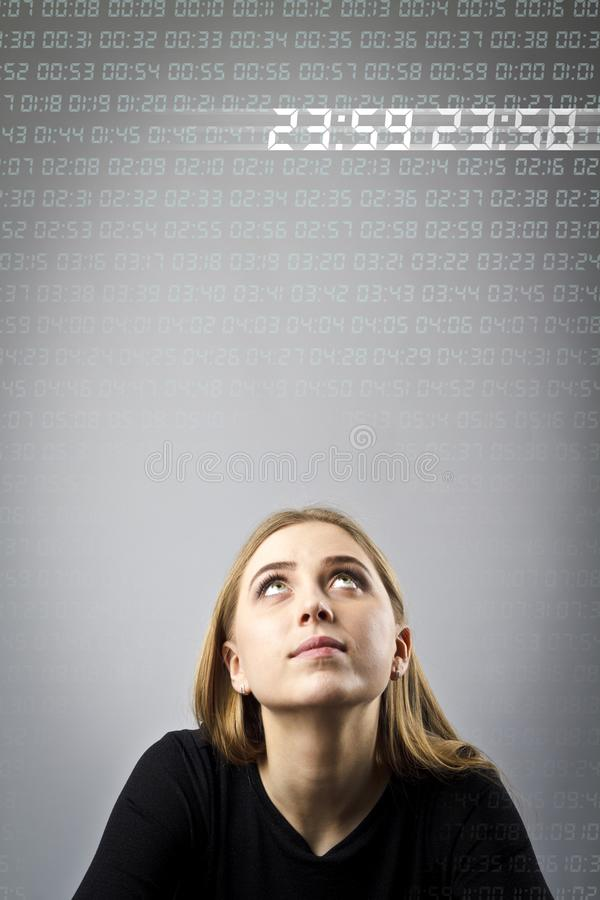 Молодая женщина в черноте и времени Время цифров проходит За немногие секунды до 12 стоковая фотография