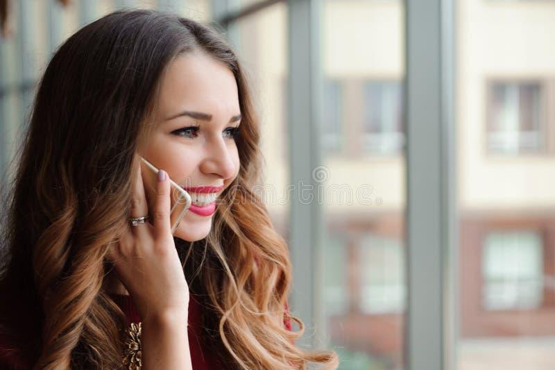 Молодая женщина говоря по телефону в аэропорте стоковые фото