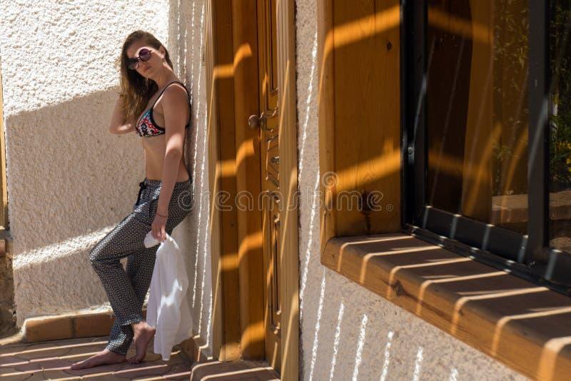 Молодая женщина красоты полагаясь на стене здания стоковое изображение