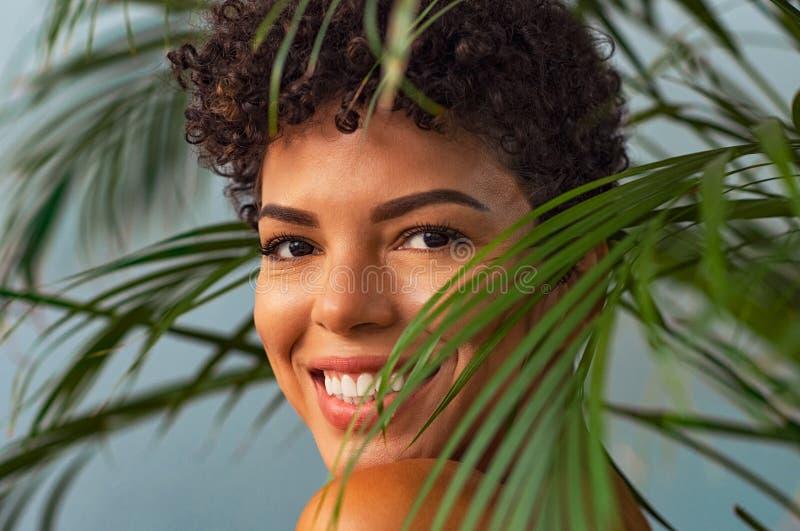 Молодая женщина красоты усмехаясь через листья ладони стоковое фото