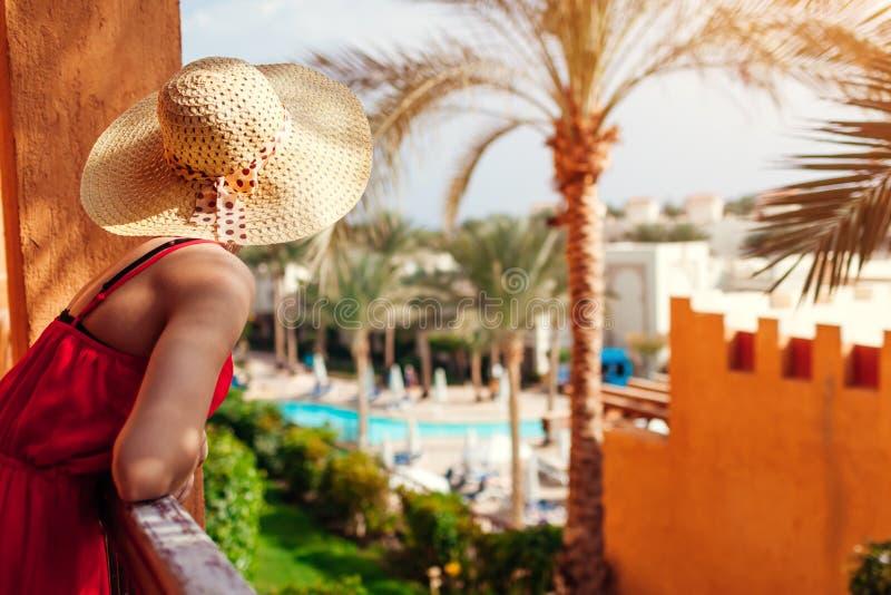 Молодая женщина наслаждаясь взглядом от балкона гостиницы в Египте Иметь полезного время работы в тропическом курорте стоковое изображение