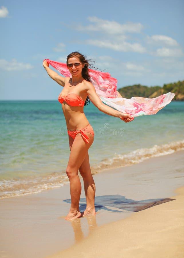 Молодая женщина пригонки в красных бикини и солнечных очках, стойках на пляже, держа розовый шарф развевая в ветре за ей Штиль на стоковое фото rf