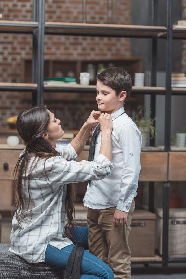 Молодая женщина помогая ее маленькому сыну получить одетый и связать галстук стоковые фотографии rf