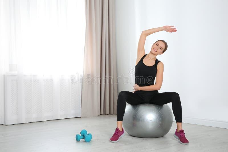 Молодая женщина делая тренировки фитнеса дома стоковые изображения rf