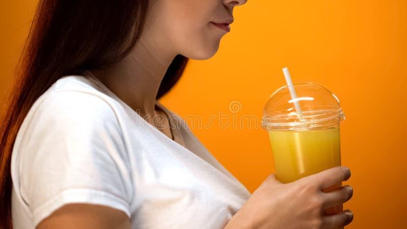 Молодая женщина держа апельсиновый сок и усмехаясь, напитки здорового питания, витамины стоковые фотографии rf