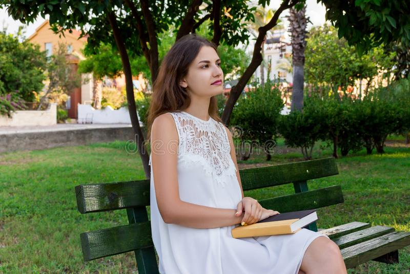 Молодая женщина сидит на стенде в парке и думает о чего она читала стоковое изображение rf