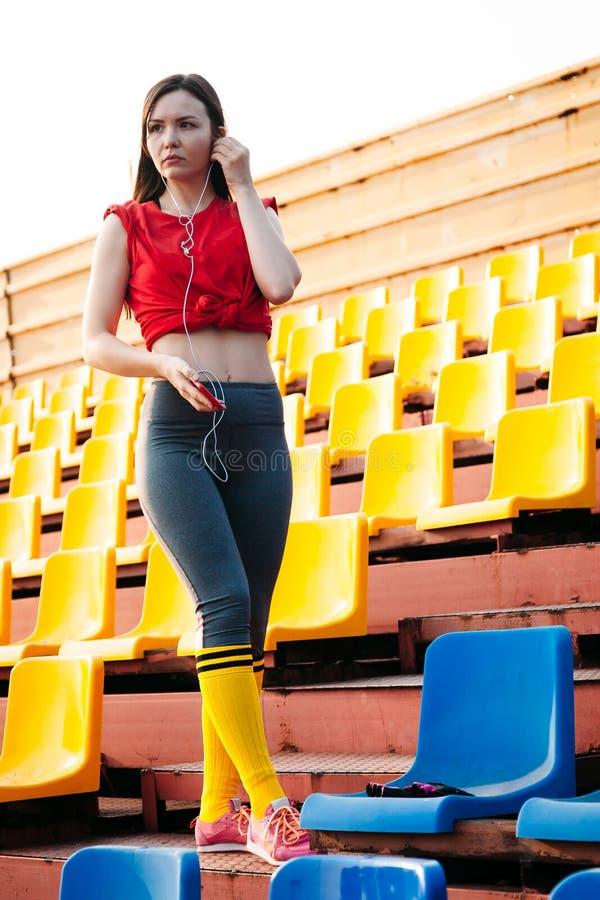 Молодая женщина спорт в sportswear на стойках стадиона слушая музыку на наушниках по телефону стоковое фото