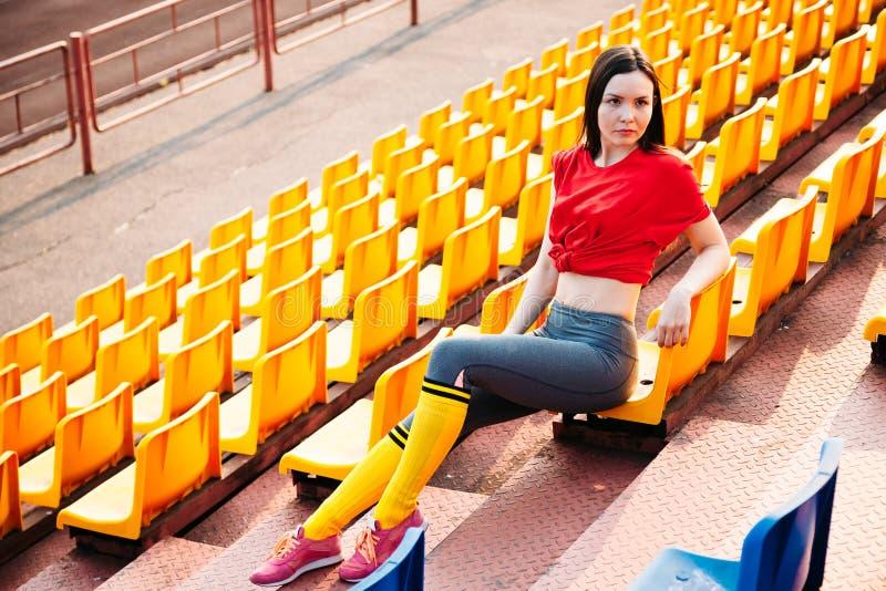 Молодая женщина спорт в sportswear на трибуне стадиона сидит на стенде стоковая фотография