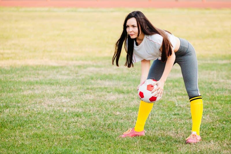 Молодая женщина спорт в sportswear на футбольном поле с шариком стоковая фотография rf