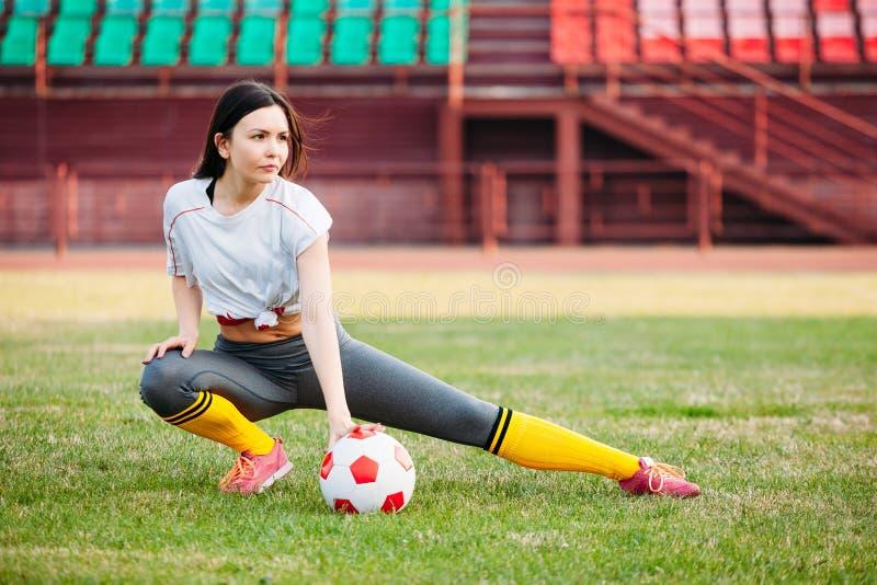 Молодая женщина спорт в sportswear на футбольном поле с шариком стоковые фотографии rf