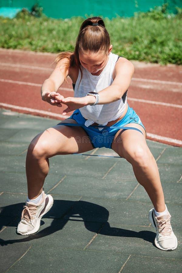 Молодая женщина спорт делая сидения на корточках с эластичной резиновой лентой фитнеса стоковое фото