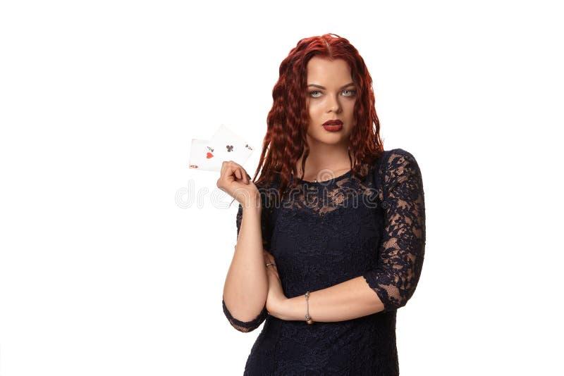 Молодая женщина с длинными красными волосами в обмундировании вечера, держа игральные карты Изолировано на белизне покер стоковые изображения rf