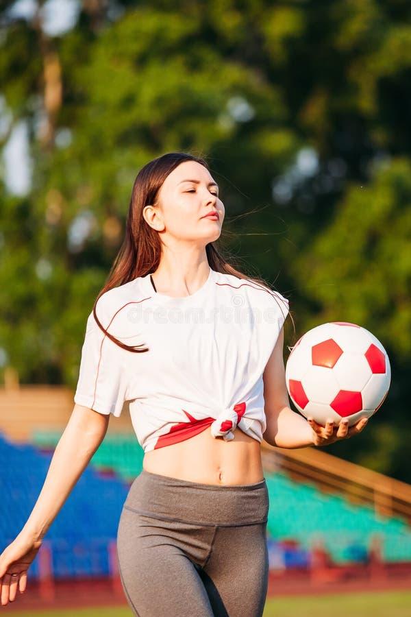 Молодая женщина с футбольным мячом в ее руках на футбольном поле на предпосылке стоек стоковые фотографии rf