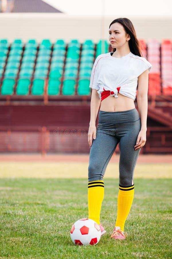 Молодая женщина с футбольным мячом на стадионе стоковые изображения