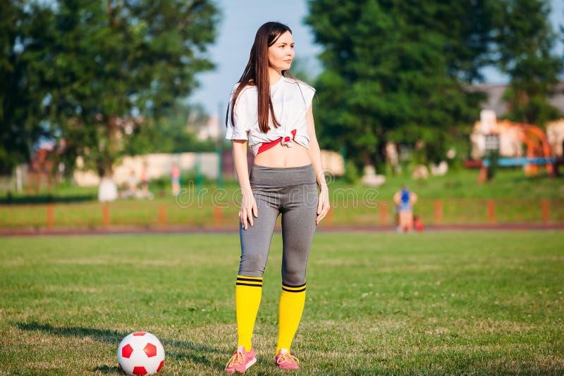 Молодая женщина с футбольным мячом на стадионе стоковое фото rf