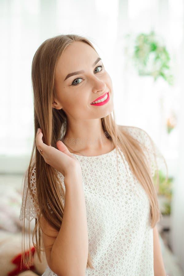 Молодая женщина усмехаясь и смотря камеру стоковые изображения