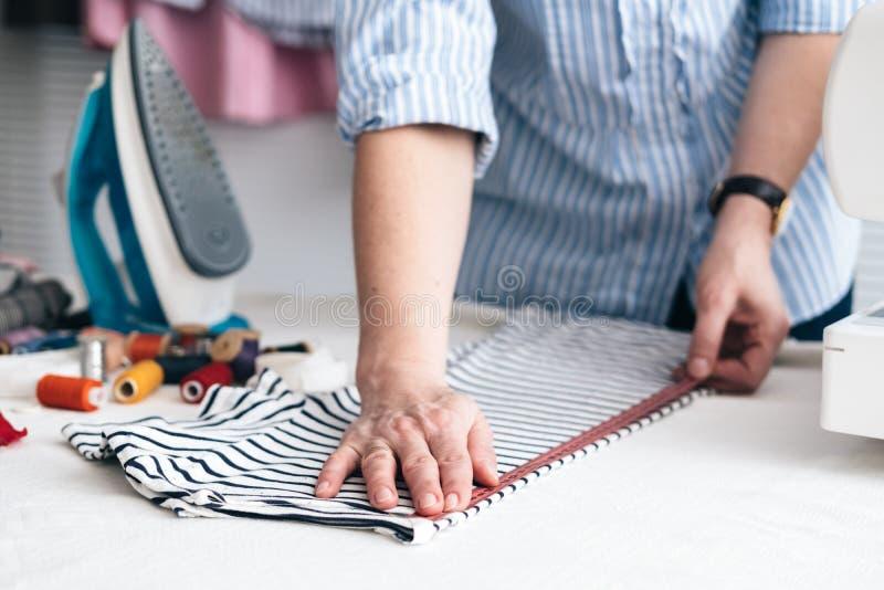 Молодая женщина работая с измеряя лентой в магазине портноя стоковые изображения rf
