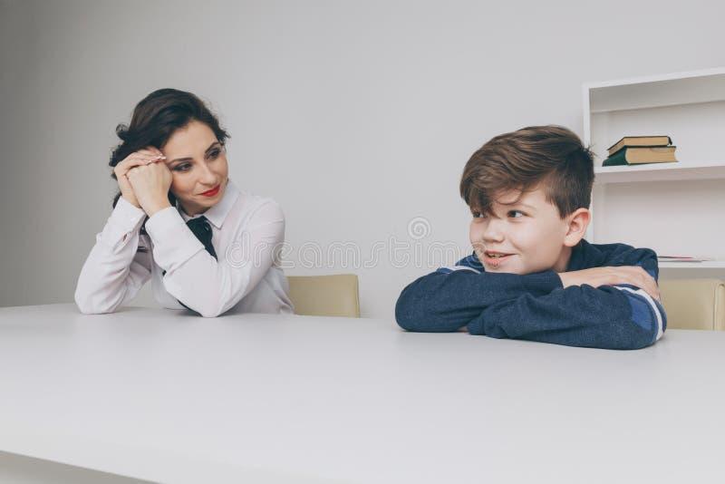 Молодая женщина brunnette говоря с мальчиком крытым белую комнату Женщина психолога с patiant Терапия психологии стоковые фотографии rf