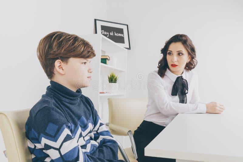 Молодая женщина brunnette говоря с мальчиком крытым белую комнату Женщина психолога с patiant Терапия психологии стоковые изображения rf