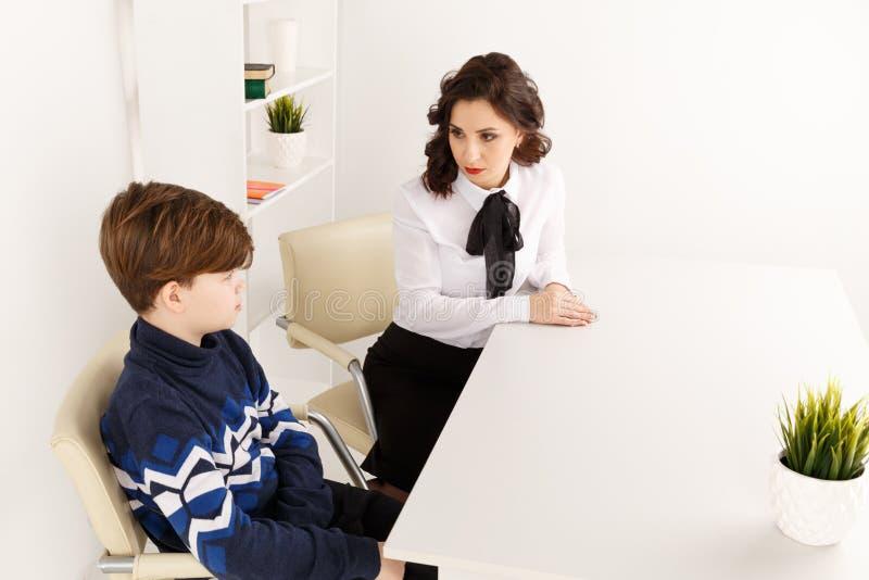 Молодая женщина brunnette говоря с мальчиком крытым белую комнату Женщина психолога с patiant Терапия психологии стоковое фото rf