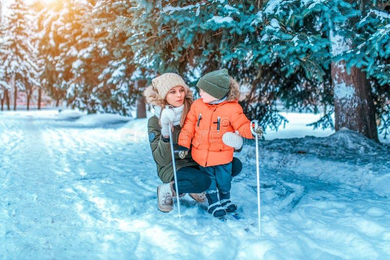 Молодая и красивая мать, учит сыну мальчика 2-4 летам старым, для того чтобы стоять на кататься на лыжах детей зимы Открытый косм стоковое изображение rf