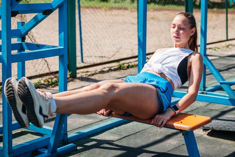 Молодая красивая атлетическая женщина трясет прессу на земле спорт стоковые изображения