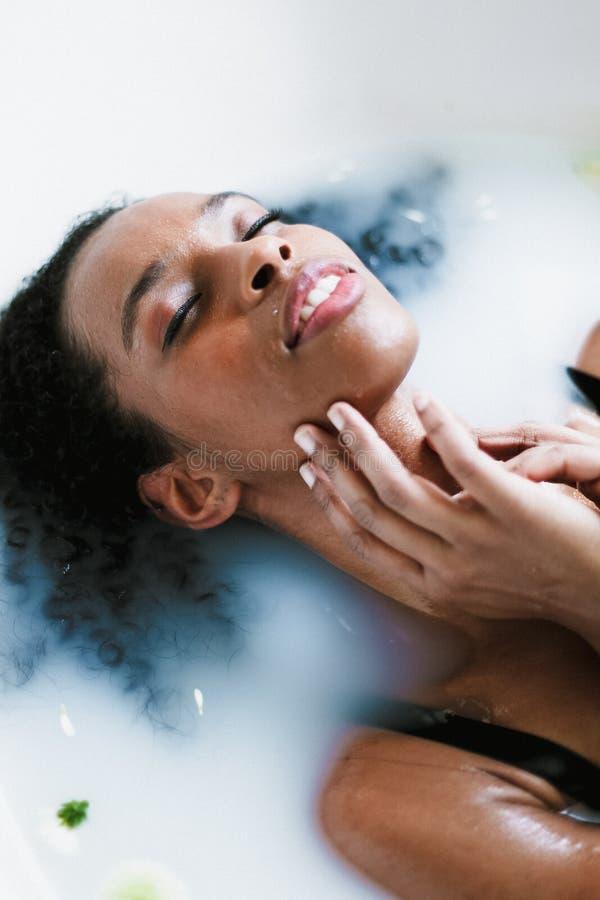 Молодая красивая афро американская девушка принимая ванну и лежа в пене, нося купальнике стоковое фото rf