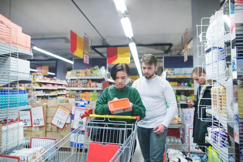 Молодая, красивая пара выбирает товары для дома в супермаркете Покупки семьи в магазине стоковые изображения rf
