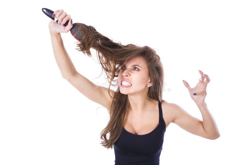 Молодая красивая девушка имея проблемы пока волосы Изолированная съемка студии стоковая фотография