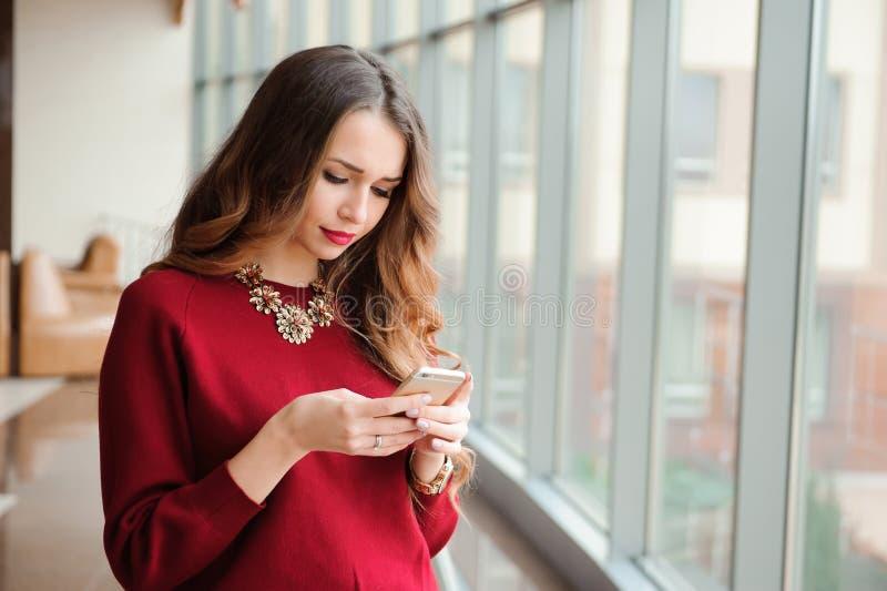 Молодая коммерсантка с мобильным телефоном около окна стоковые изображения rf